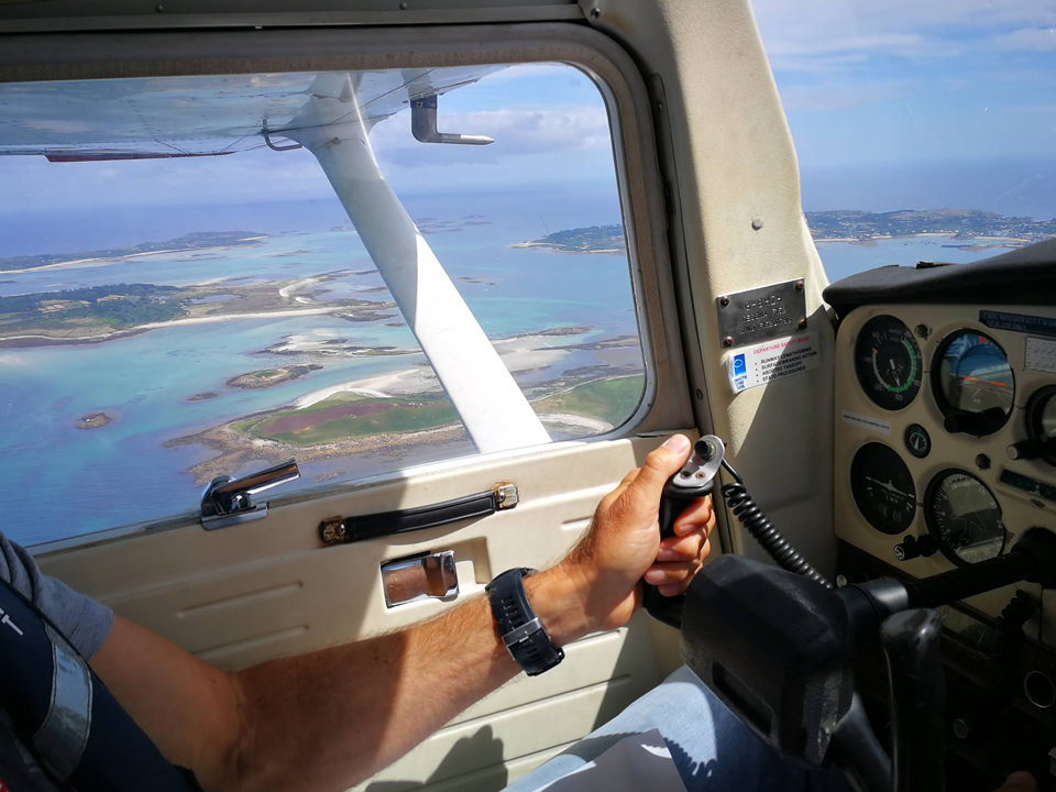Student pilot at the controls of the Cessna 152 flying over the Isles of Scilly, Cornwall.